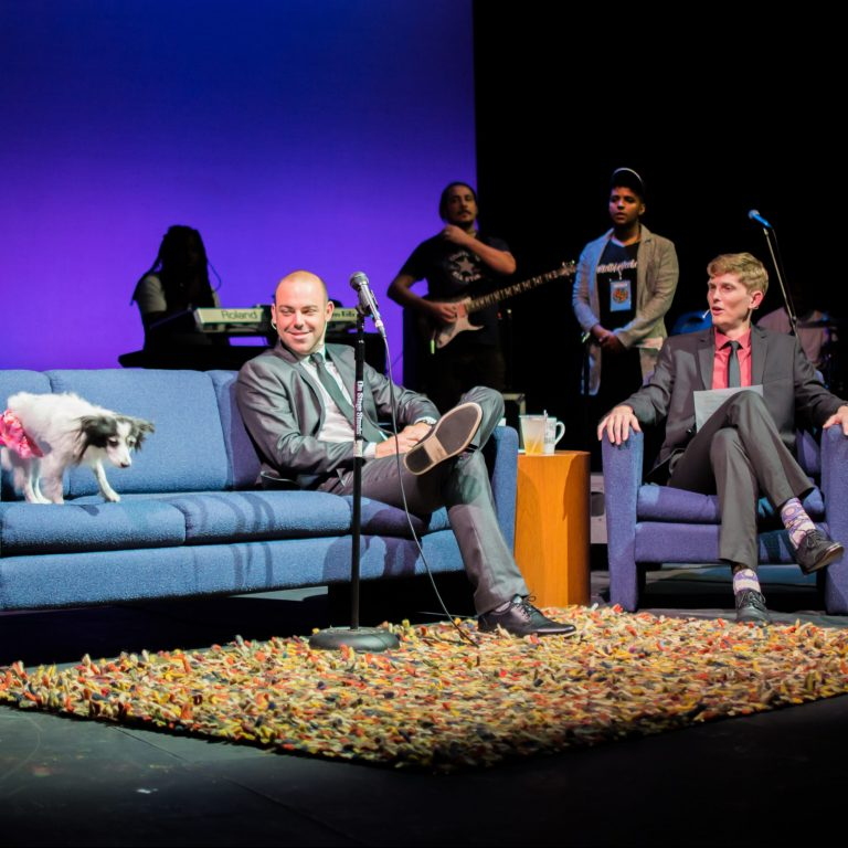 """Photo from """"Tonight at Midnight with Rauce Padgett"""" as he and his co-hose watch a dog on the far side of the interview couch."""