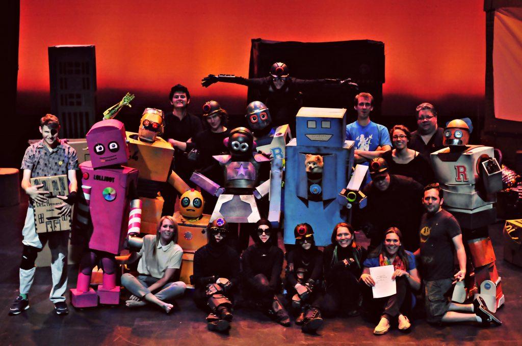 Photo of a cast in costume with some people in cardboard robot costumes