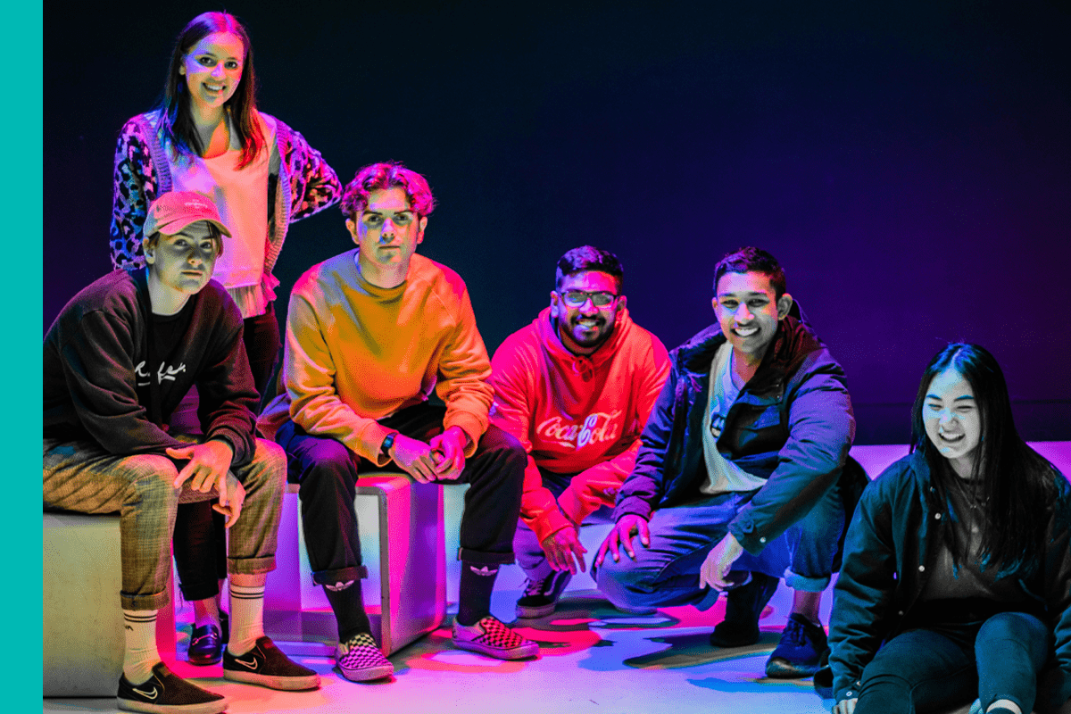 Photo of four teens sitting on a stage with colorful lighting