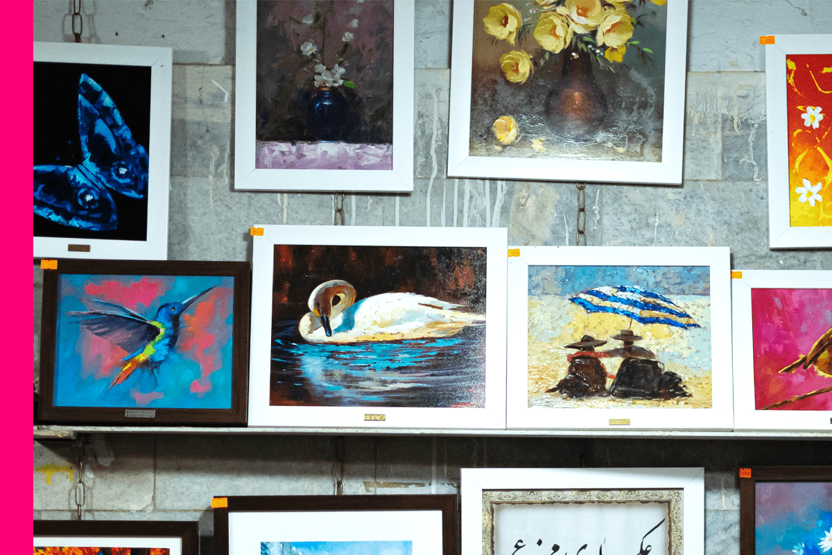 Photo of framed paintings on a wall.