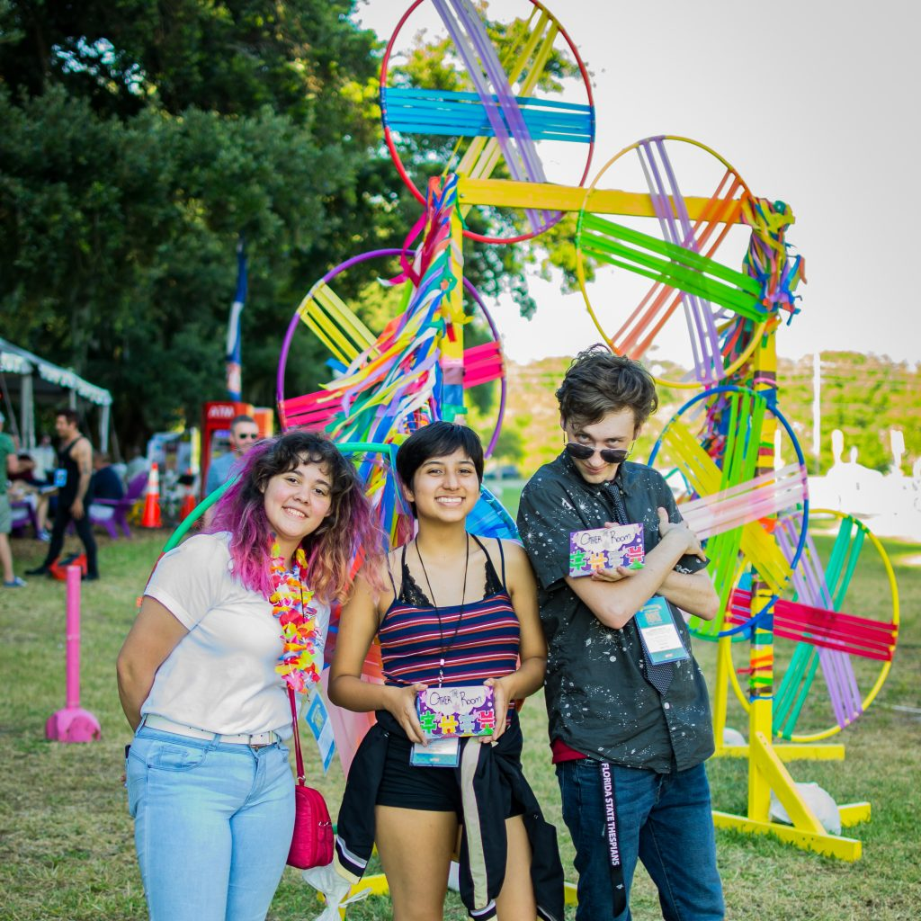 Photo of three people standing in front of an art sculpture consisting of colored hoops and ribbons.