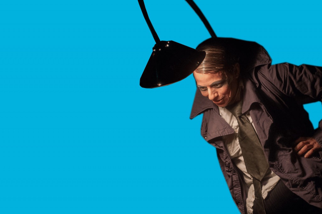 A performer in a trench coat with a lamp post coming from their back and a lamp shinning on their face.