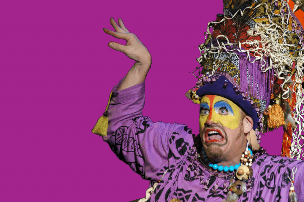Photo of a performer with bright colored face paint and an ornate head dress.