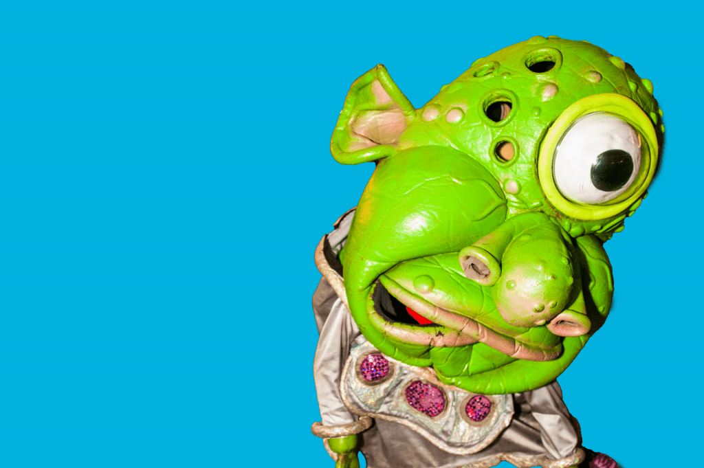 A green alien looking creature costume with one eye.