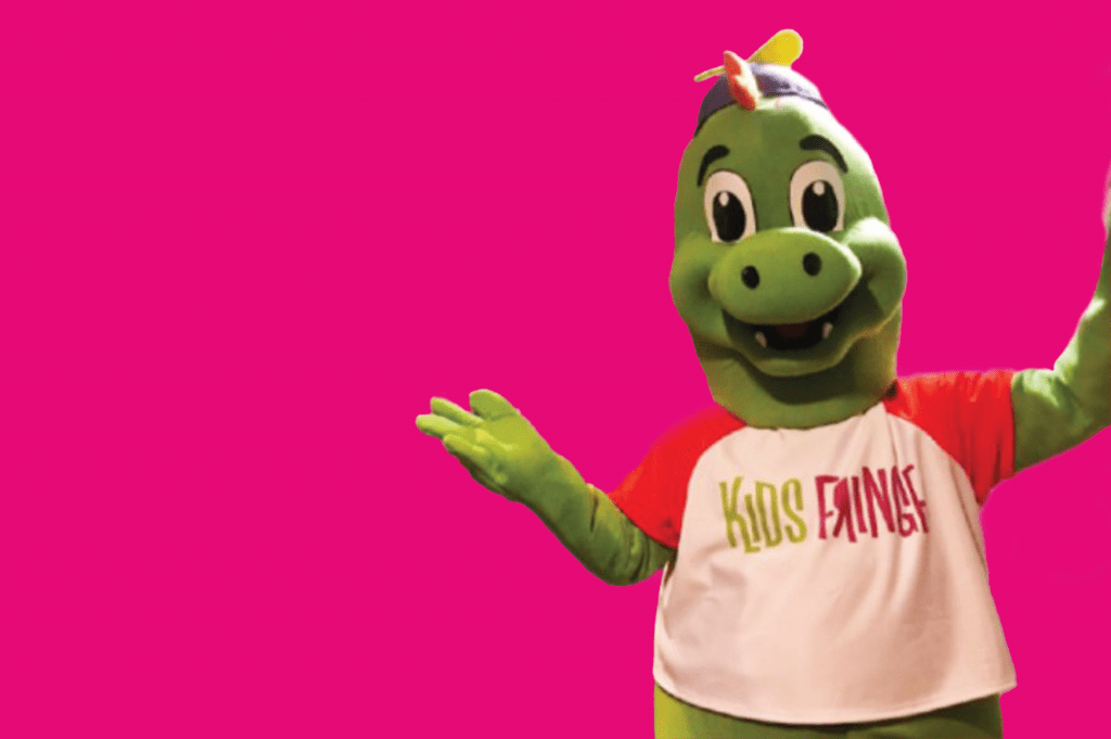 Fringezilla, the mascot of Fringe is a green dinosaur with a smile on his face, a beanie hat, and a Kids Fringe t-shirt.