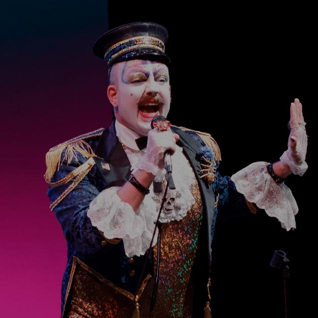 Photo of Dandy Darkly. A clown looking man in a train conductors uniform