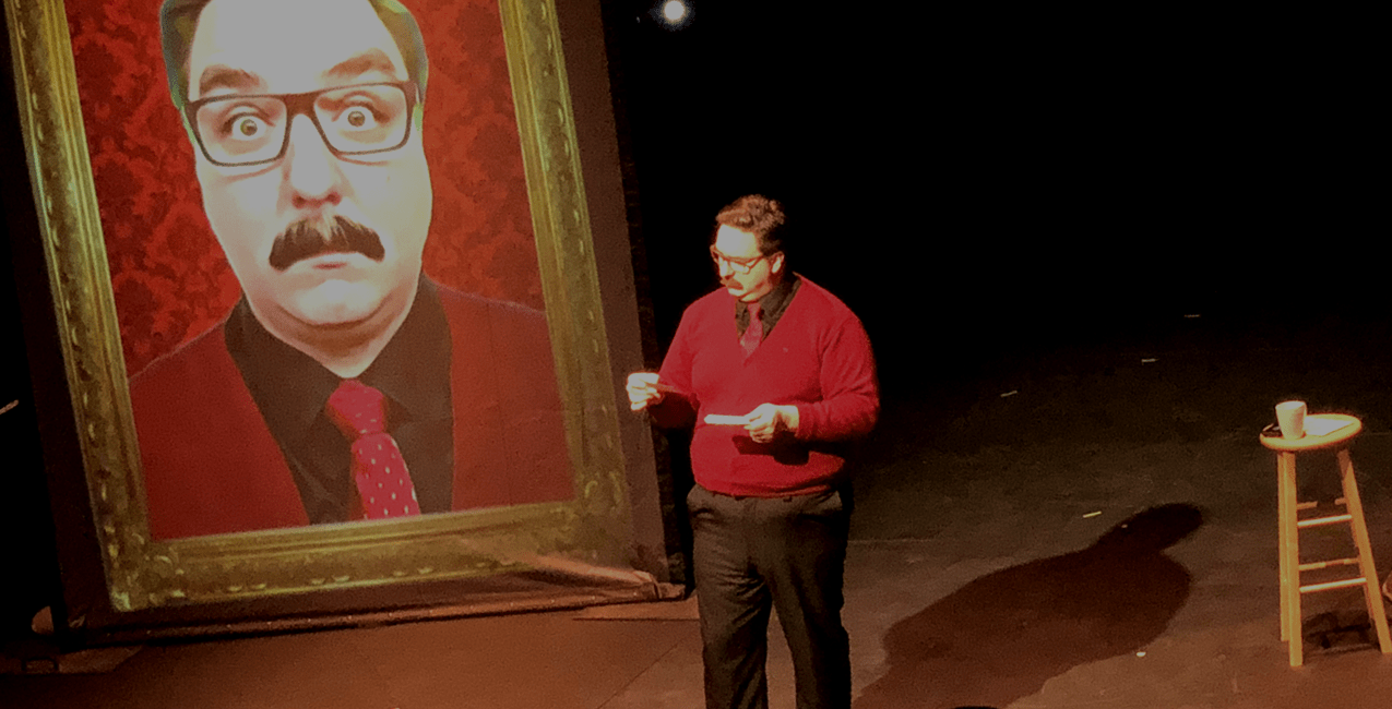 Performer with glasses and a mustache, dressed in black pants, with a red sweater and tie.