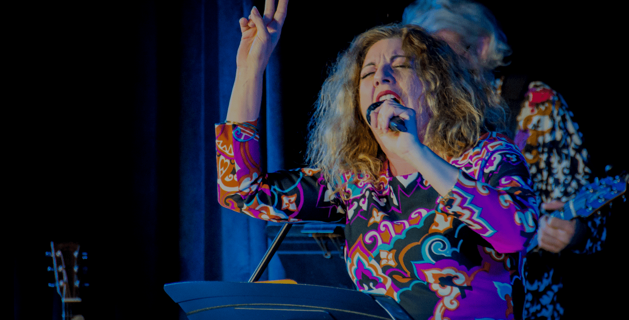 A performer, Janine Klien singing passionately on stage.