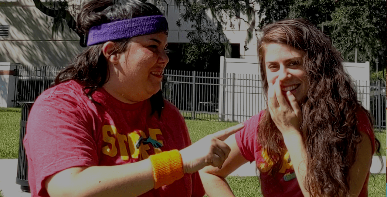 Lisa and Lindsay laughing. Lindsay is dressed in a colorful athletic headband and wrist bands.