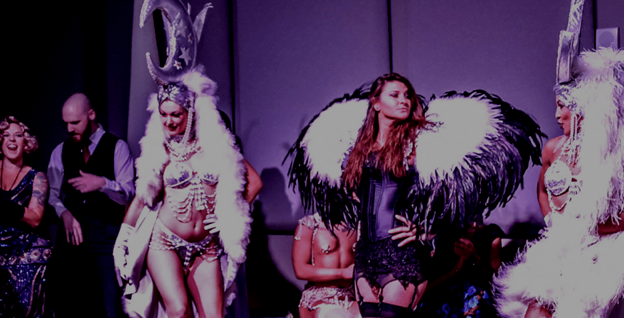 Photo from a themed performance. A women is central wearing a silver burlesque-style outfit with ornate headdress. There are other woman behind her also in 1920's burlesque costumes.
