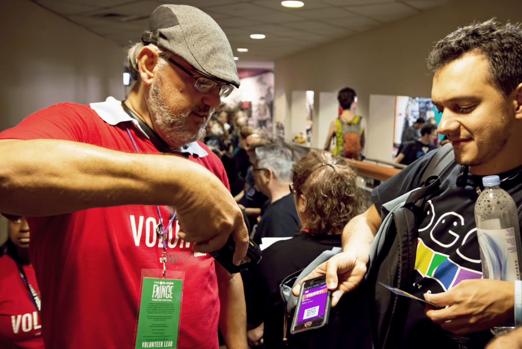Photo of a volunteer scanning a ticket on a patrons phone