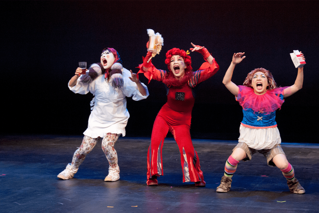 A trio of Japanese artists performing on a stage
