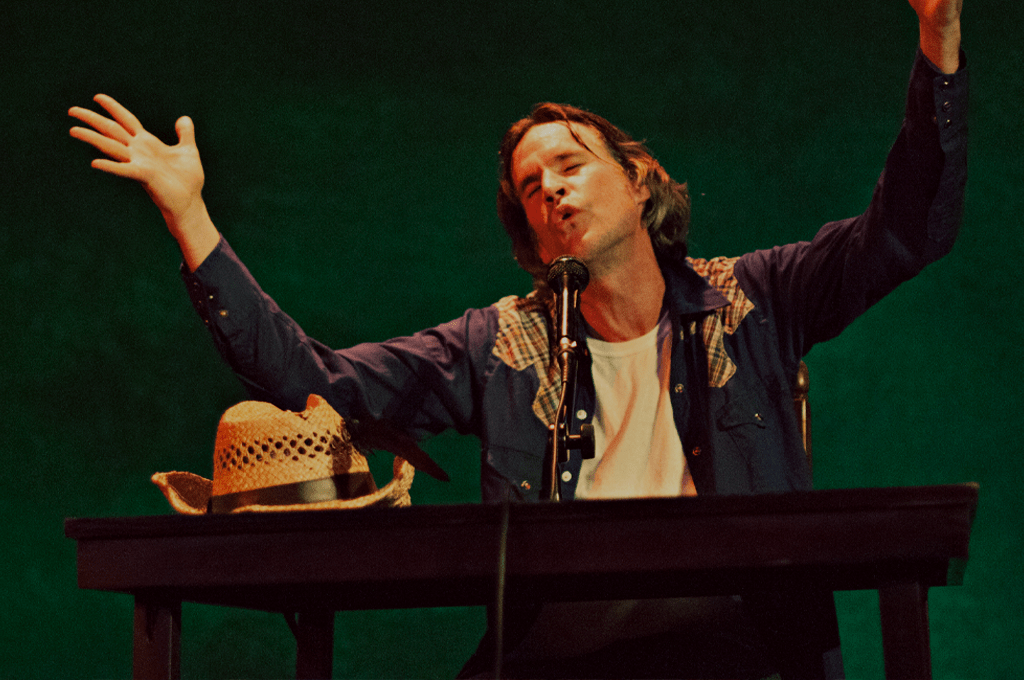 Photo of a male performer sitting behind a desk, speaking passionately into a microphone with his arms in the air. There is a cowboy hat on the desk and a dark green background behind him.