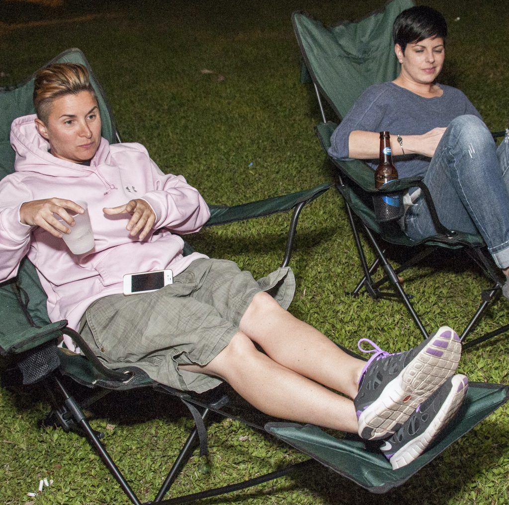 Photo of two people sitting in chairs on the grass a comfortable distance from each other.