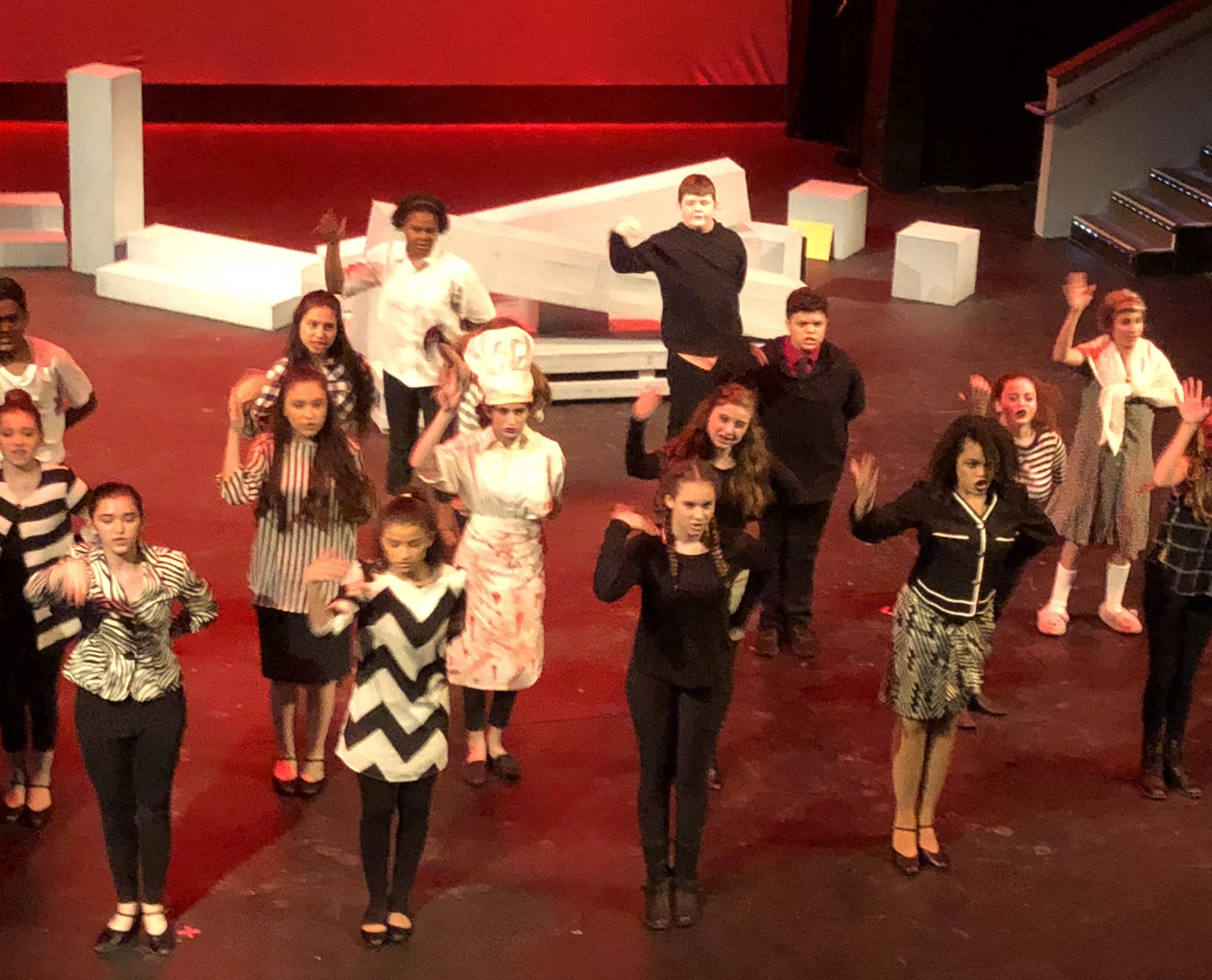 Photo of a cast of teen performers on stage.