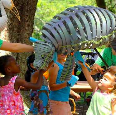 Photo of two children looking at and touching a manatee puppet suspended above them.