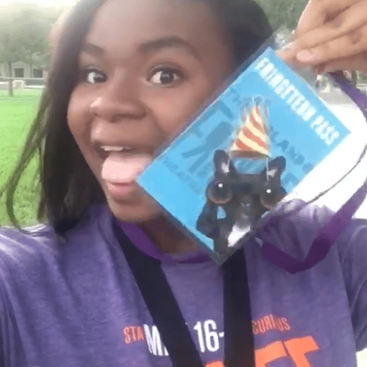 Photo of a Fringetern smiling and holding up an all-access pass to the festival