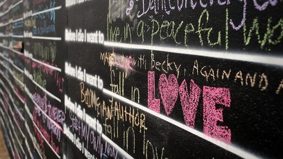 """Close up photo of the """"Before I Die Wall"""" an art installation at Fringe."""