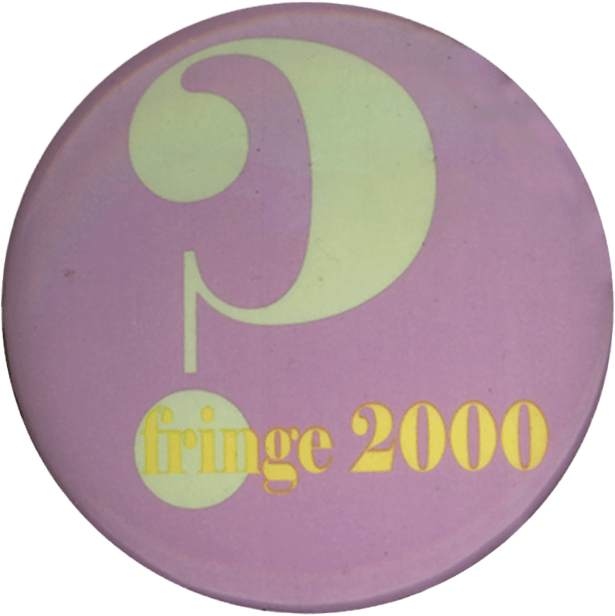 A round button with a tan colored questions mark with Fringe 2000 on it.