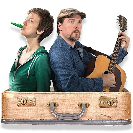 Two people in a suitcase facing back-to-back. Man is playing guitar. Women is blowing into a kazoo.