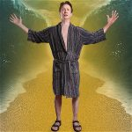 A man in dark robe stands with his arms out and hands pointed upwards. What appears to be ocean water is to the left and right of him.
