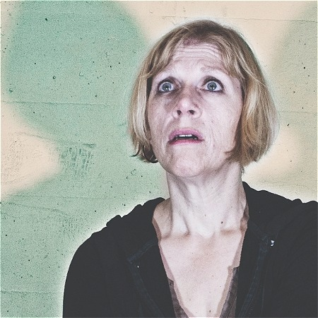 A woman looks upwards and has a frightened facial expression. Shadows are visible behind her.