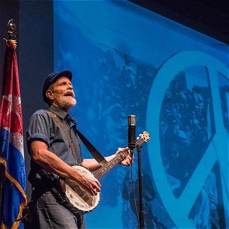 A man is playing a guitar. To the left of him is a flag on a flagpole. To the right of him is what appears to be a blue flag with a peace sign on it displayed on a wall.