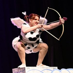 A woman dressed as what appears to be Cupid holds a bow and heart shaped arrow.