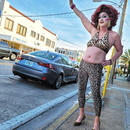 A person wearing cheetah print pants and a bikini top stands on a street sidewalk with their arm up as if hailing a taxi. There are cars in the street and a building on the opposite side.