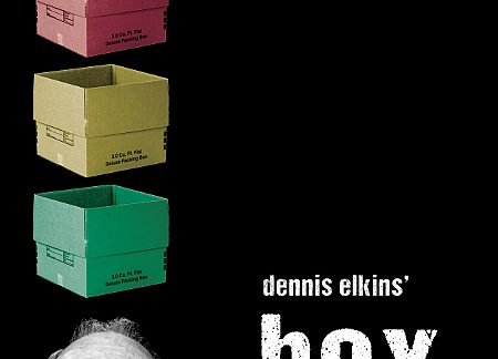 """Man looking up at a green, yellow, and red box stacked up above his head. Text says """"dennis elkins' box."""""""