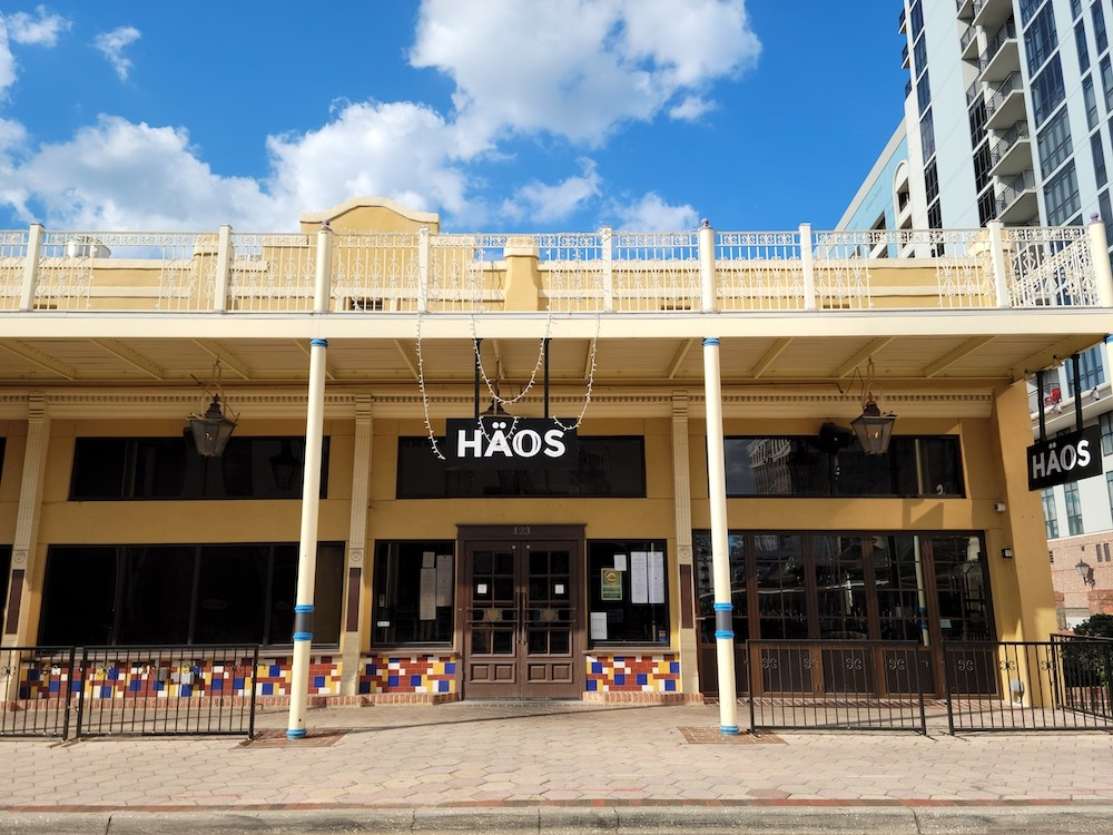 """Photo of the HÄOS on Church exterior. It is a yellow two-story building with the word """"HÄOS"""" on a black sign hanging in front of the door. There is a balcony above the door. There are lights strung from the top of the balcony to the bottom by the door."""