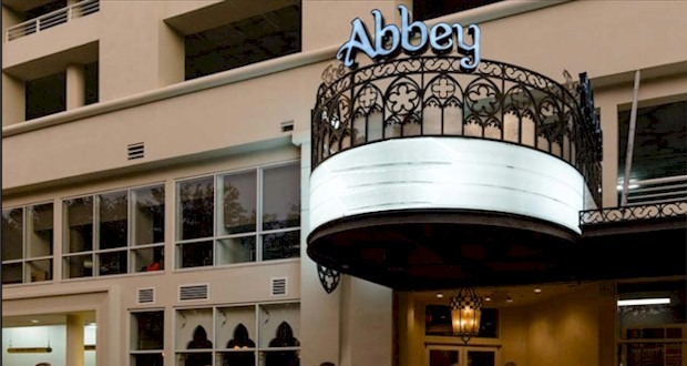 Exterior photo of the Abbey. A beige building with a ornate marquee extending out of the building over the entrance. The words The Abbey are above a railing above the marque.