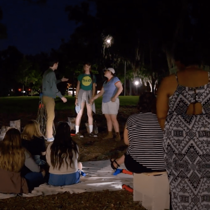 Photo of actors performing outside with patrons sitting and standing around them.
